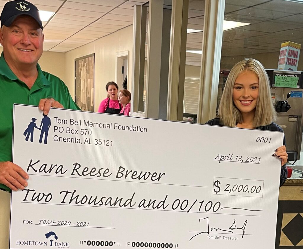 Kara Reese Brewer (right) is presented the annual Tom Bell Scholarship by Bill Hendrickson. -courtesy Tom Bell Memorial Foundation