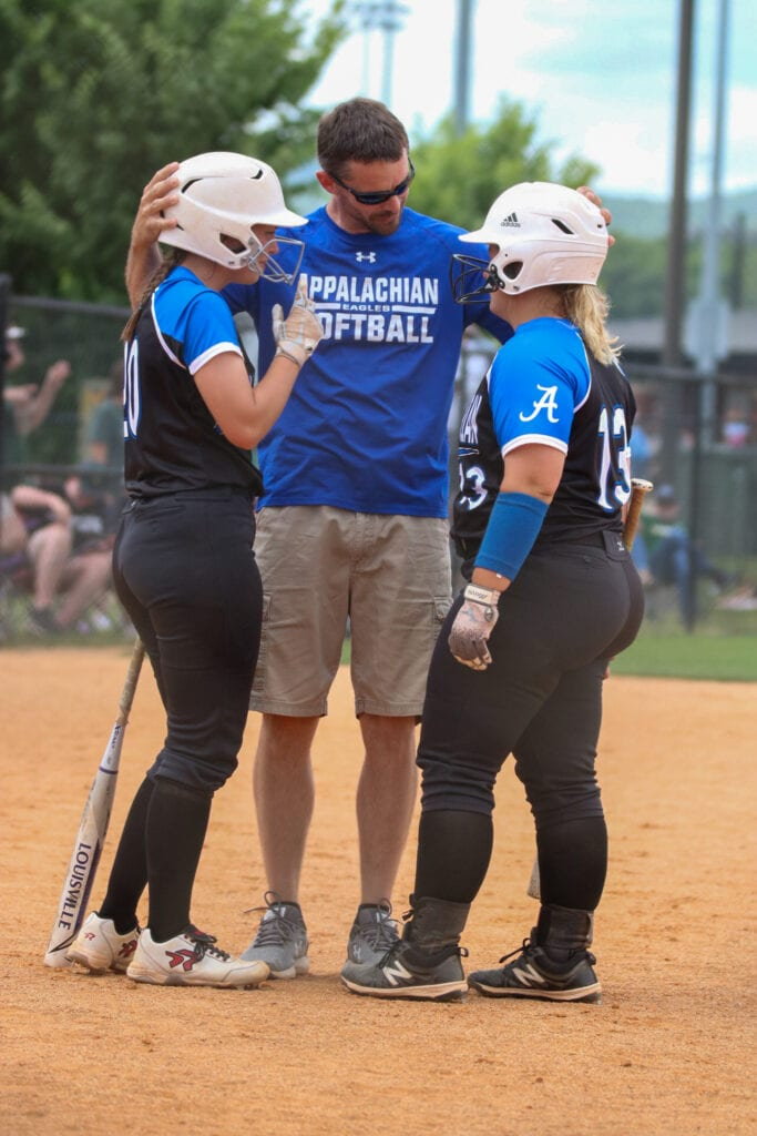 Coach Laurence Martin gives instruction and encouragement to Zoe Payne (20) and Jordan Henderson (13). -Mandy Moore Photography