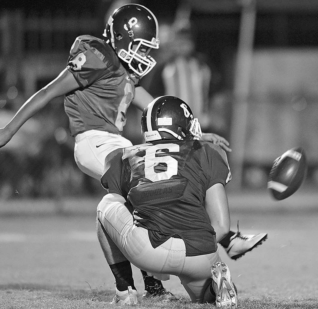 Locust Fork's Jose Hernandez drills an extra point with help from holder Tyler Clevenger. -www.southernexposurephotos.com