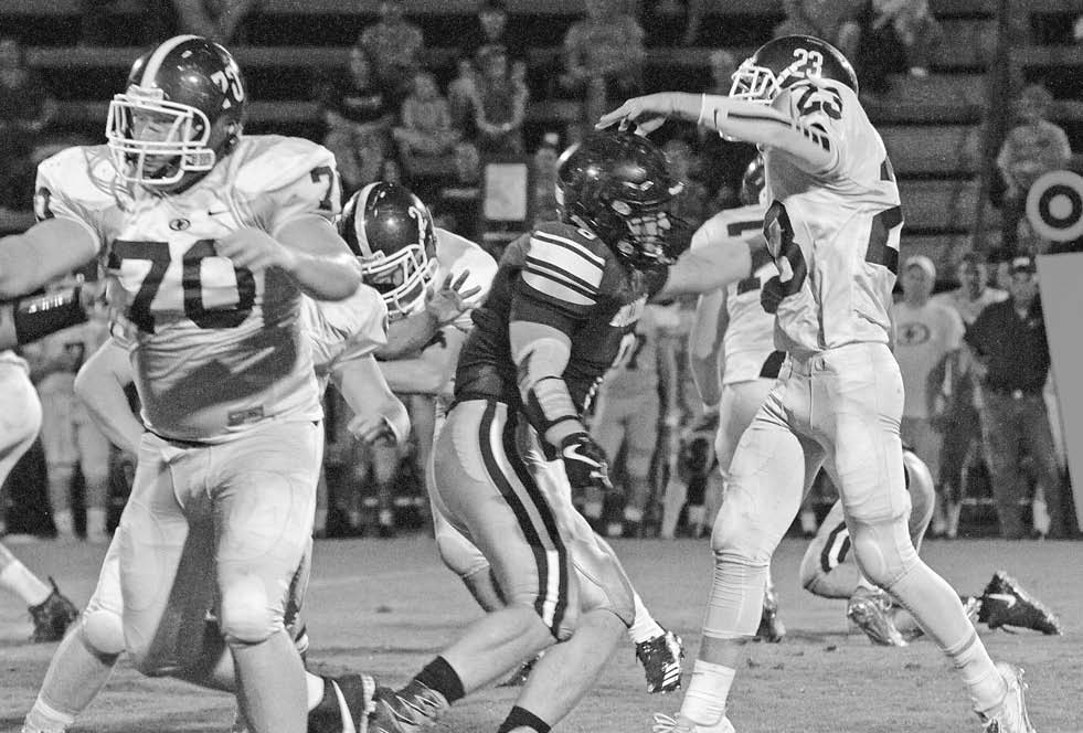 Locust Fork quarterback Charlie Cater releases a pass despite the pressure from Susan Moore's Ross Thompson. -Keith Standridge