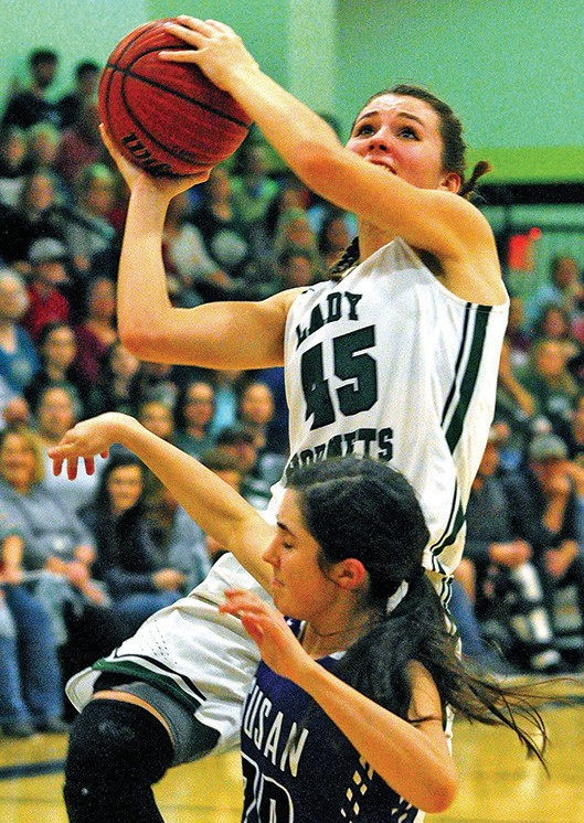 Locust Fork's Rachael Baker (45) puts up a shot over the Susan Moore defense during Saturday varsity girls championship game of the Blount County Tournament. Locust Fork won the title game 75-48 over the Lady Bulldogs. -Keith Standridge