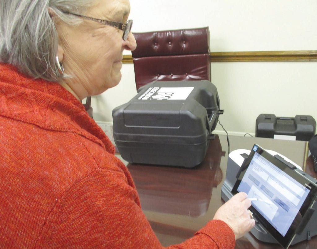 Chief probate clerk (retired) Bonnie Monty demonstrates use of a new electronic poll book being evaluated for use throughout the county.