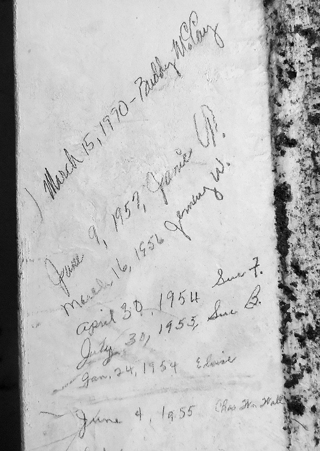 Inset: Names and dates written on the cement door jamb of the vault range from the 1940s to 1990.