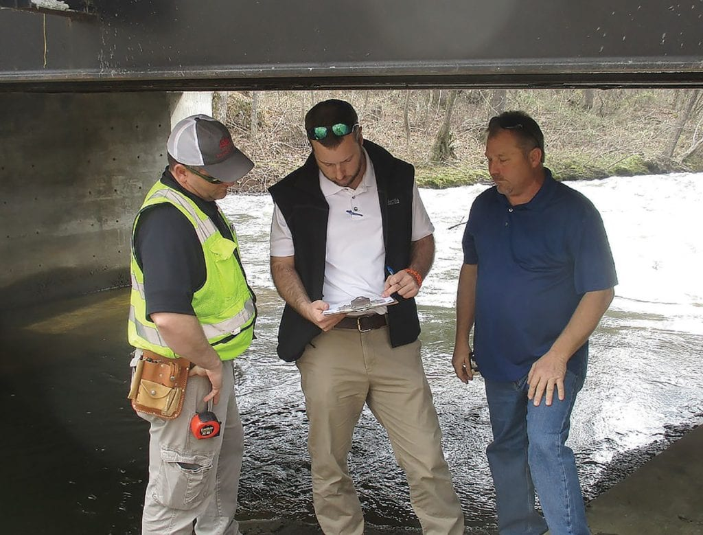 From left: assistant bridge inspector Brad Holland, county engineer Dustin Stewart, and District 3 Commissioner Dean Calvert confer over inspection data for River Road Bridge, recently rebuilt, widened to two lanes and strengthened with abutments and steel support members. Awaiting Alabama Department of Transportation approval to remove all weight restrictions.
