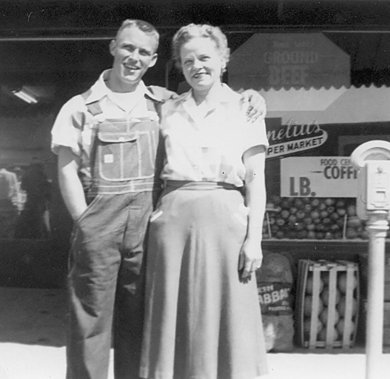 Talmage and Grace Cornelius outside their store. Tal sports overalls for Blue Bell Day.