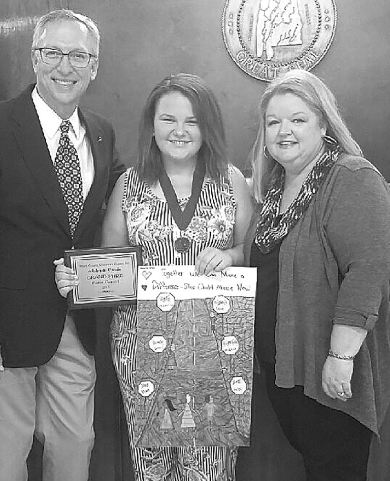 Jim Ed Clayton (left), Children's Center executive director, and Judge Sherry Burns (right) congratulate Adalayda Uptain, a Locust Fork sixth grader and grand prize poster contest winner. -Blount County Children's Center
