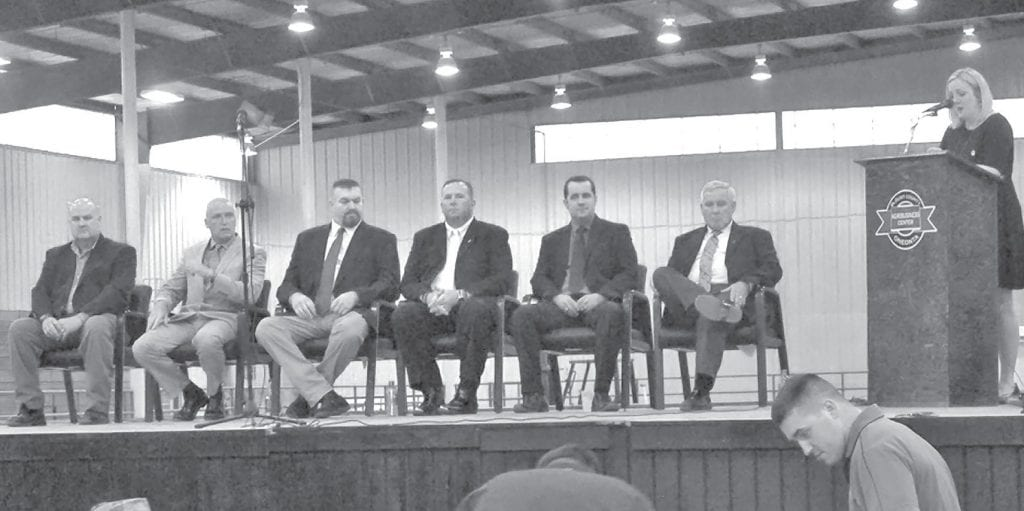 Candidates for Blount County Sheriff meet at the Agri-Business Center for a public forum in preparation for the primary election June 5. From left: Ron Chastain, Kevin Price, Charlie Turner, Mark Moon, Chase Ramsey, and James Chapman. District Attorney Pamela Casey, standing at right, moderated the event.
