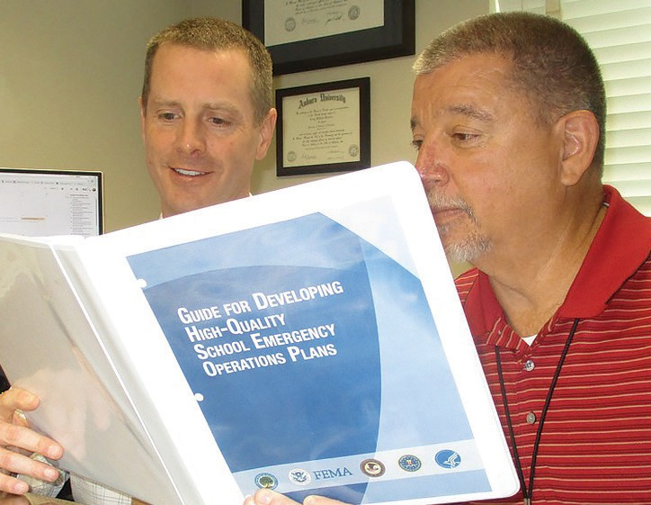Major players pose with Blount County Schools' safety and security bible. From left, Blount County Schools federal program coordinator Craig Sosebee and Emergency Management Agency director (and tabletop expert) Don Roybal. The binder is definitive, having been blessed by the U.S. Departments of Education, Health and Human Services, Homeland Security, and Justice, plus the FBI, and FEMA.