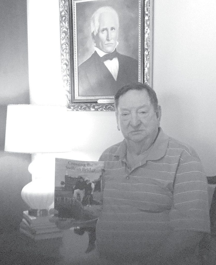 Dr. Joe Brindley sits in front of a portrait of his great-grandfather, Mace Thomas Payne Brindley, at Joe's Limestone Springs home while holding a copy of his just released book, Crossing the Swilcan Bridge.