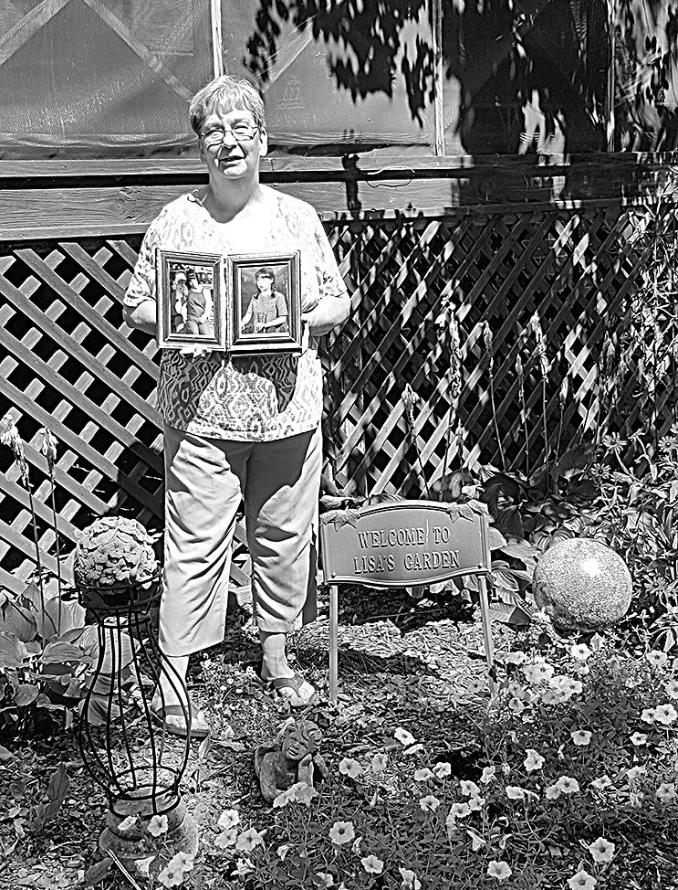 Barbara Gilliland holds photos of daughter Lisa in Lisa's Garden.