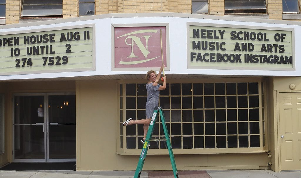 Deborah Beason works to give the Neely Theater marquee a facelift in time for the Aug. 11 open house. Meanwhile the marquee keeps on doing its job announcing what's coming up next.