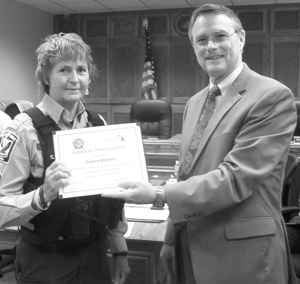 Blount County Jail employee Caroline Bearden, left, receives a Certificate of Completion for the training course sponsored by the National Institute of Jail Operations. Probate Judge Chris Green makes the presentation.