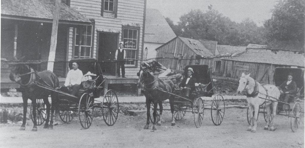 Blountsville Post Office ca. 1920. In buggies, Will Tidwell, Otto Graves (postmaster), and Monroe Graves. Mr. Bynum at post office door. Blackwood house to left and old Baptist church and blacksmith shop to the right.