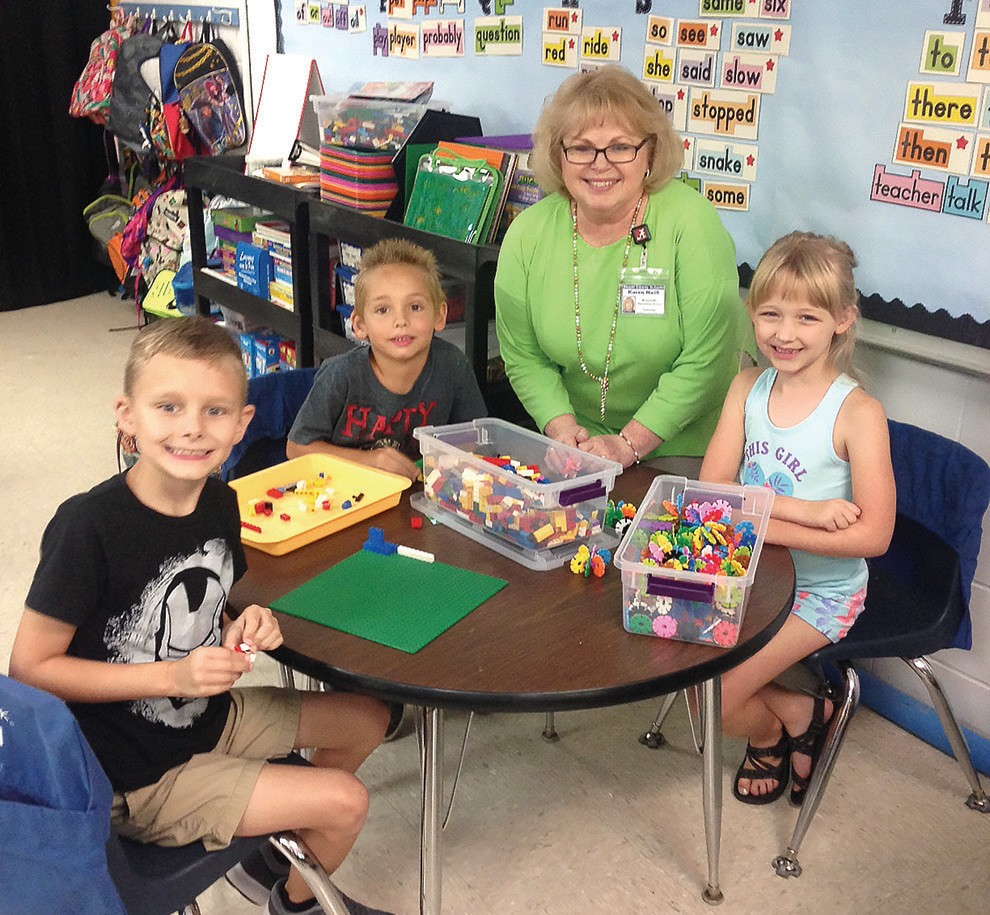 Karen Neill, first grade teacher at Blountsville Elementary, pauses during hands-on learning time with Ian Floyd, Daniel Stillwell, and Bella Walker.