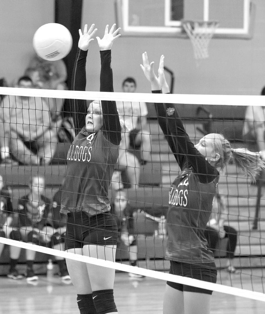 Susan Moore's Mekenzie Standridge (left) and Lacey Floyd attempt to block a hit. -Sherrie Abercrombie