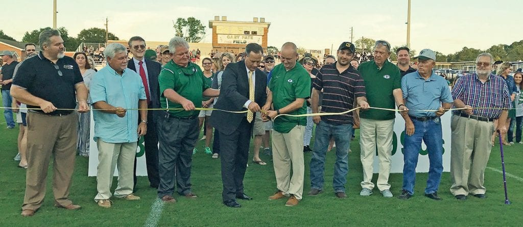 Blount County Board of Education Superintendent Rodney Green and Locust Fork High School Principal Tommy Smitherman (center) cut the ribbon for the new Locust Fork High School football stadium as dignitaries and alumni look on Friday night. -Lisa Baker