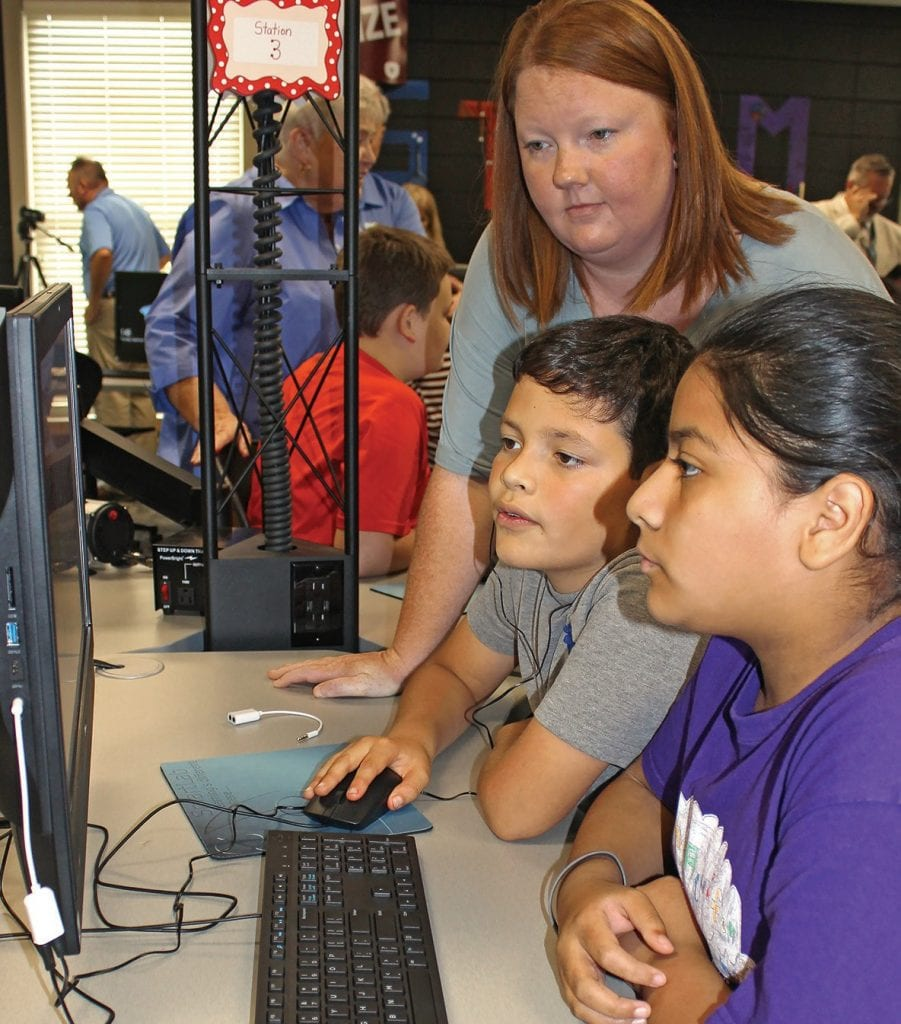 Johnna Pannell (standing) observes fifth-graders Ana Gabriela Calderon and Isaac Mejia as they work on one of the many stations in the new Susan Moore STEAM lab.