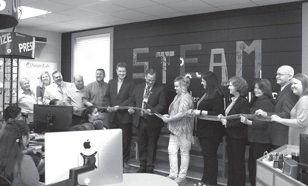 Thirteen individuals involved in implementing the Susan Moore STEAM lab project form a chorus line at the ribbon cutting celebration last week. From left, Jackie Sivley, Blount County Board of Education; Sarah Smith, Schneider Electric; Stoney Beavers, Blount County Schools assistant superintendent; Jim Henderson, Blount County Education Foundation; Mike Stansberry, Susan Moore High School principal; Todd Smith, Schneider Electric; Rodney Green, Blount County Schools superintendent; Jennifer Priest, STEAM lab teacher/facilitator; Tammy McMinn, Susan Moore Elementary School principal; Bridgette Murphree, Blount County Schools elementary curriculum coordinator; Danna and Rep. David Standridge; and Johnna Pannell, representing the Blount County - Oneonta Chamber of Commerce.