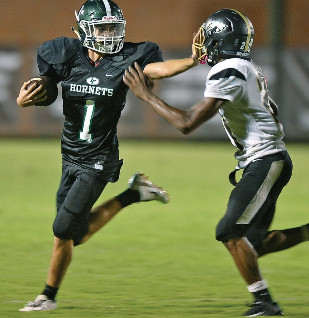 Locust Fork's Ben Oden (1) stiff arms an East Lawrence defender. -www.southernexposurephotos.com