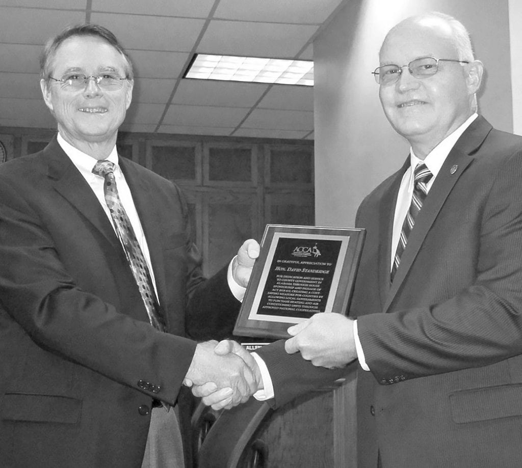 Commission Chairman Chris Green awards Rep. David Standridge a commemorative plaque expressing appreciation for sponsoring legislation creating a cost-saving measure for counties. It does so by allowing local governments to purchase HVAC units through approved national cooperatives. (Before the act passed, competitive bids were required for those entities to purchase HVAC systems exceeding $50,000.)