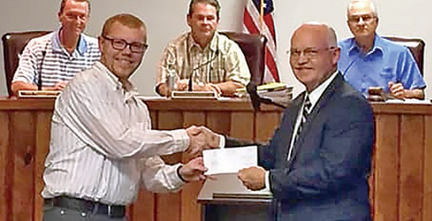 Oneonta Public Library director Ricky Statham (left) accepts a check from Rep. David Standridge during the Oct. 9 Oneonta City Council meeting. -Facebook | Rep. David Standridge