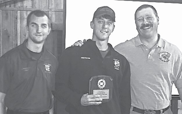 Assistant fire chief Wesley Cox (left) and fire chief Jon Head (right) congratulate Chance Payne on being named firefighter of the year. -Jonathan Ledbetter