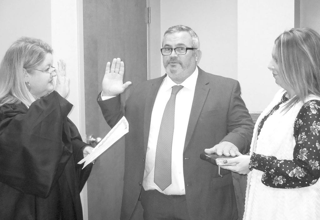 District 1 Commissioner Allen Armstrong is sworn in for his third term. From left, District Judge Sherry Burns, Armstrong, and Stephanie Lovell, assisting in the ceremony.