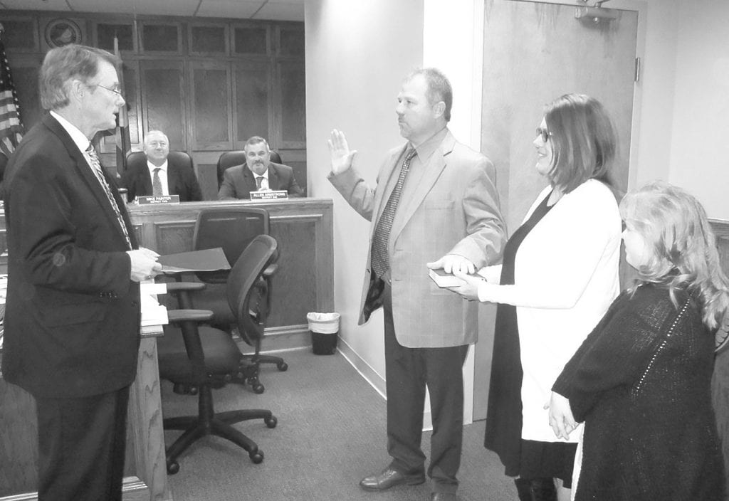 District 3 Commissioner Dean Calvert is sworn in for his third term. From left, Commission Chairman Chris Green, Calvert, wife Sheila, and daughter Gracie.