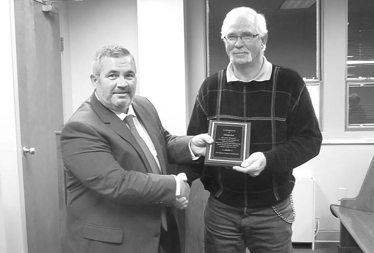 District 1 Commissioner Allen Armstrong, left, presents Glennis Best a plaque of appreciation for his 35 years of service to the county. Best served in recent years as District 1 road crew foreman.