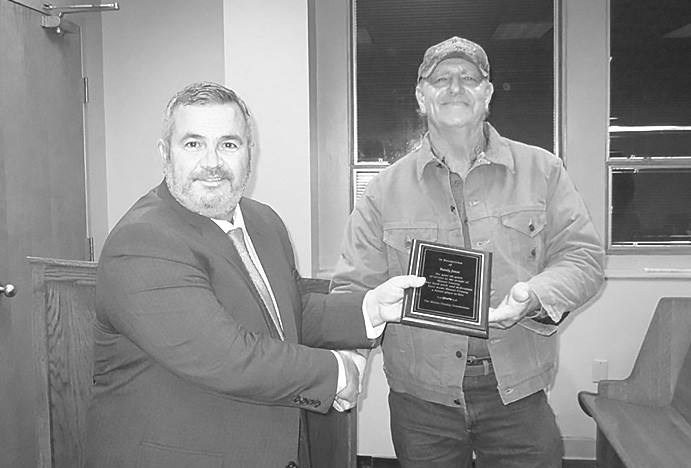 Allen Armstrong, left, presents Randy Jones a plaque of appreciation for his 36 years of service to the county. He served District 1 residents under five different county commissioners.