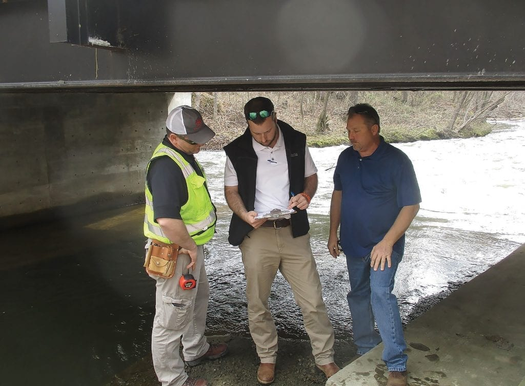 Feb. 28, 2018: From left: assistant bridge inspector Brad Holland, county engineer Dustin Stewart, and District 3 Commissioner Dean Calvert confer over inspection data for River Road Bridge, recently rebuilt, widened to two lanes and strengthened with abutments and steel support members. Awaiting Alabama Department of Transportation approval to remove all weight restrictions.