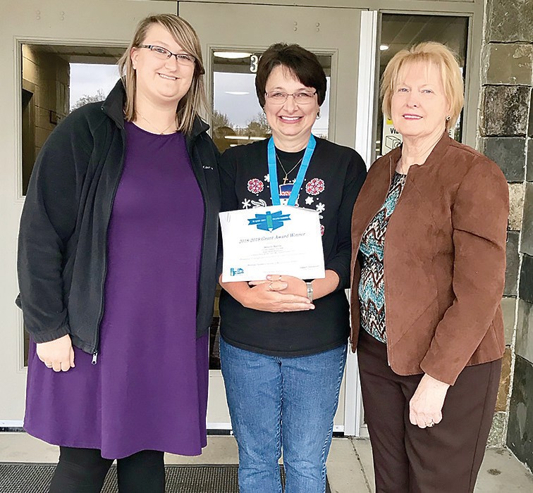 Susan Moore elementary teacher Beverly Reeves, center, displays her 2018-2019 grant award certificate. She is the first recipient of the newly-created signature endowed grant in memory of former Susan Moore coach and principal Bruce McAfee. Flanking her are (left) Kaylie Bynum, Coach Mac's granddaughter, and (right) Sarah McAfee, Coach Mac's wife.