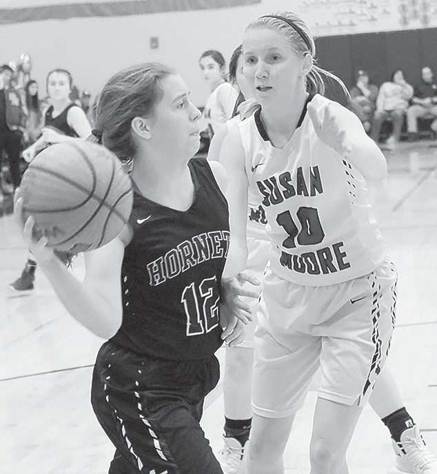 Locust Fork's Madison Roy looks to pass inside against Susan Moore's Hallie Holmes. -Brandy Wells | Blount Photographic