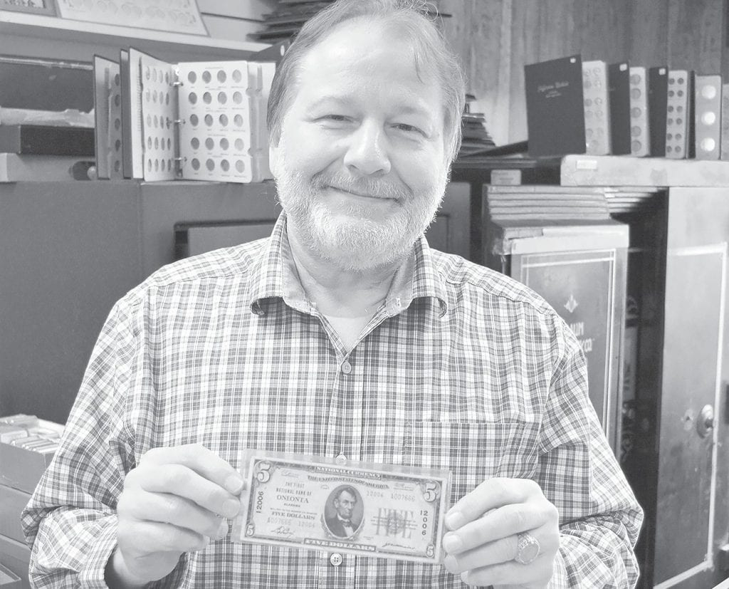 Patrick Fendley proudly displays a $5 note issued in 1929 by the First National Bank of Oneonta.