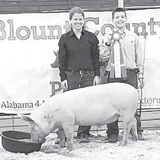 Grand champion hog exhibited by Cooper Burgess, with judge Julie Johnston.