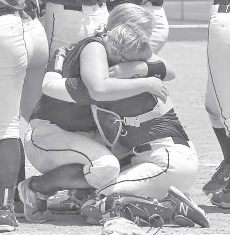 First baseman Becca Benton (left) and catcher Isabelle Johnson embrace after Saturday's championship victory. -Jennifer Kirk