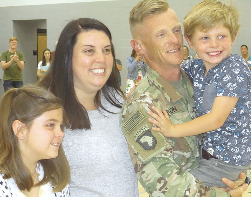 The Garten family, from left, Mallory, mother Meredith, father Jeren, and Camden. Sgt. Garten has just walked in from Iraq, joined them at a school assembly, and the kids didn't even know he was on their side of the world.