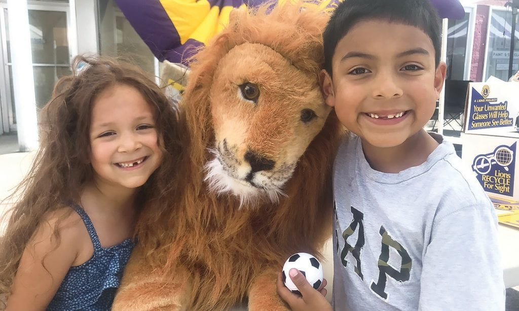 Children at Oneonta's June Fling meet Leo, the lovable lion mascot, at the Central Blount County Lions Club's first ever get-acquainted booth at a public event. With two lovable children, it was a perfect match. Besides the lovable lion, the booth featured the organization's signature fund-raising appeal – selling mops and brooms to fund its good works projects.