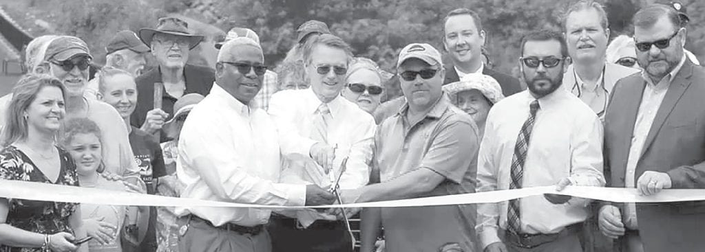 Visionaries, implementers, workers, collaborators, partners, supporters, and cheerleaders all gathered Monday morning to celebrate the grand opening of King's Bend Scenic Overlook Park. Four of the notables who helped get the project done appear near the center of the photo: DeJarvis Leonard, holding the scissors, is the east central region engineer for the Alabama Department of Transportation, a major player in the development of the project. Moving to the right is probate judge and commission chairman Chris Green, who lived with the project continuously from conception to completion; to Green's right are commissioners Dean Calvert and Nick Washburn, whose road crews provided much of the muscle resulting in the project's appearance as a natural wonder. -Tonya Hill | Facebook