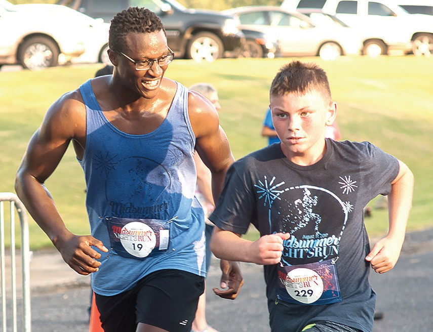 Edouard Ndecky encourages Pate Pass during the 2018 run. Inset: Families enjoying the MSNR fireworks. -photos courtesy of HomeTown Bank