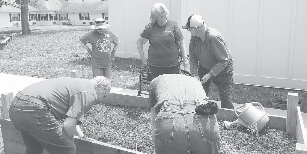 Master Gardener volunteers and TLC Nursing Center clients planting raised beds last April.