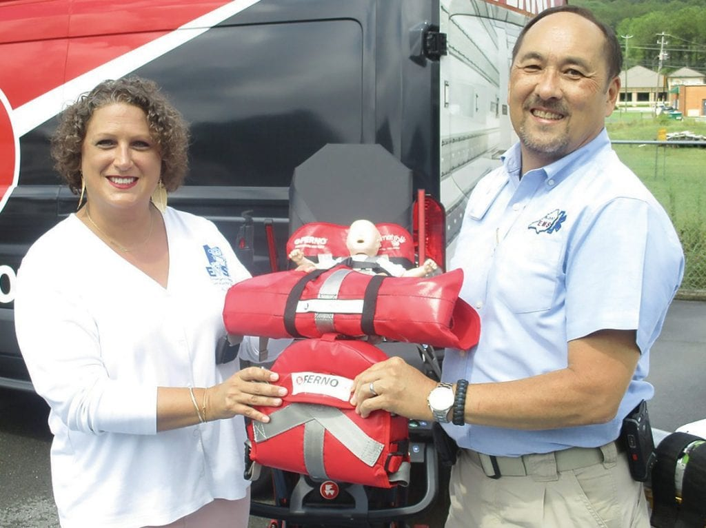 Katherine Hert, Emergency Medical Services for Children (EMSC) director for the Alabama Department of Public Health and Weslie Powell, Blount EMS Ambulance operations manager, display the pre-use compact storage packaging of the two child pediatric restraint units that will now be in use in Blount EMS ambulances. In the background, an infant is shown in the smaller of the two units, called a Neo-Mate, securely buckled to an ambulance stretcher. The Neo-Mate is for infants from 5 pounds to 14 pounds. The larger, but similar, Pedi-Mate is for children weighing from 10 pounds to 100 pounds. The van in the background belongs to Ferno, supplier of the restraint units.
