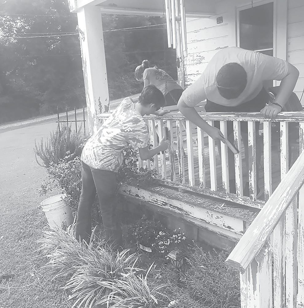 Community Changers Blake Battles, Gabriel Price, and Emily Bryant scrape old paint to prepare to repaint a porch. -Facebook