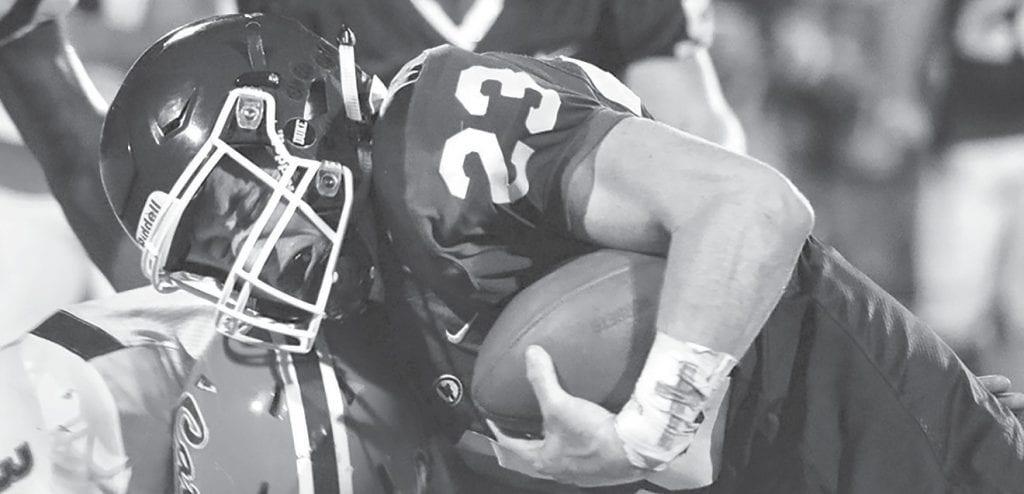 Charlie Cater (23) runs over a Fultondale defender. -Locust Fork High School Football | Facebook