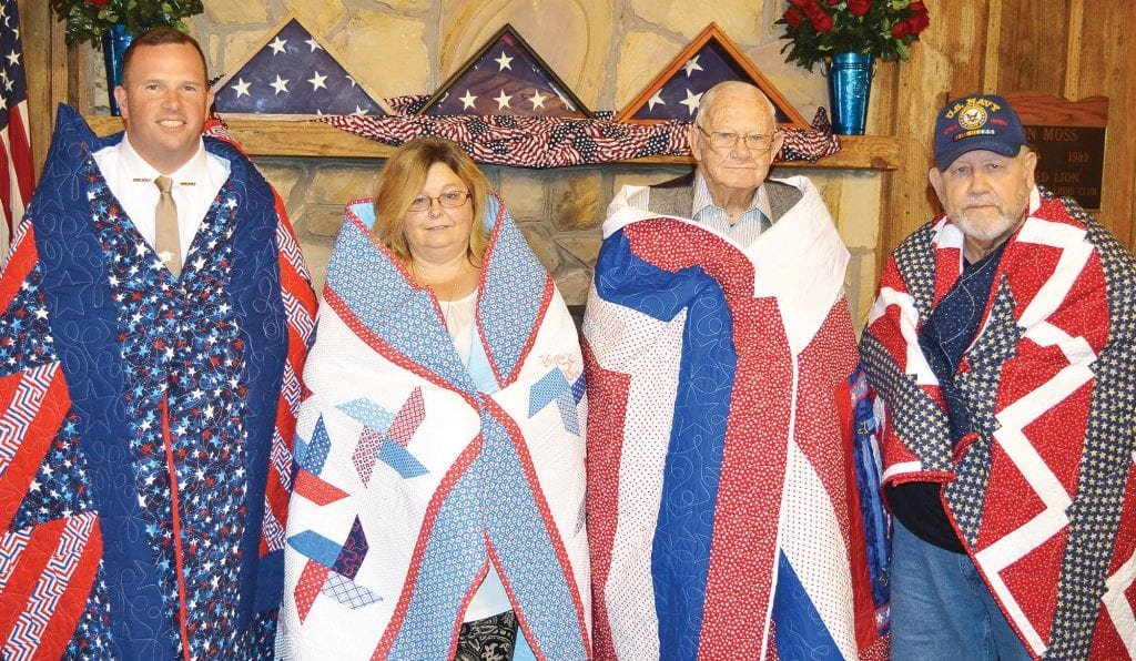 From left: Sheriff Mark Moon, Tammy Glover, James Tolbert, and Ronnie Rutledge (accepting for John Anthony Mahan) model their quilts.