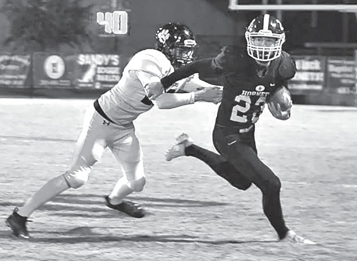 Charlie Cater (23) evades a tackle and tucks the ball to run. -Locust Fork Fooball | Facebook