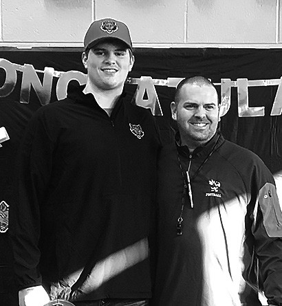 Noah Smith (left) is congratulated by Locust Fork head coach Matt Plunkett.