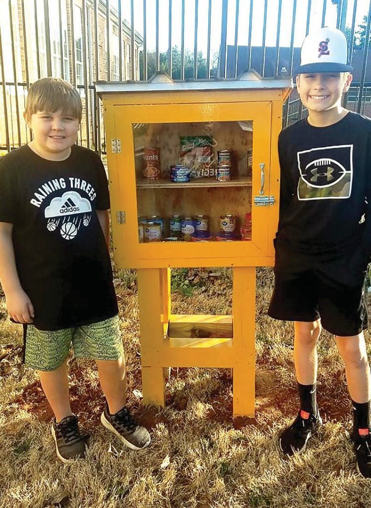 Jacob (left) and Isaac Buettner check Hayden's Free Food Pantry. -Keisha Reid