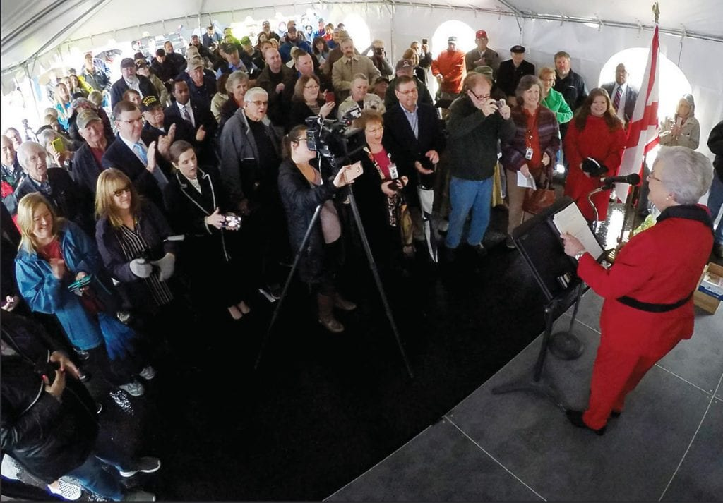 Gov. Kay Ivey good humoredly suggests that the majority standing-room crowd take a seat – if they can find one – during the Freedom Bridge dedication Monday. -Blount County Commission | Facebook