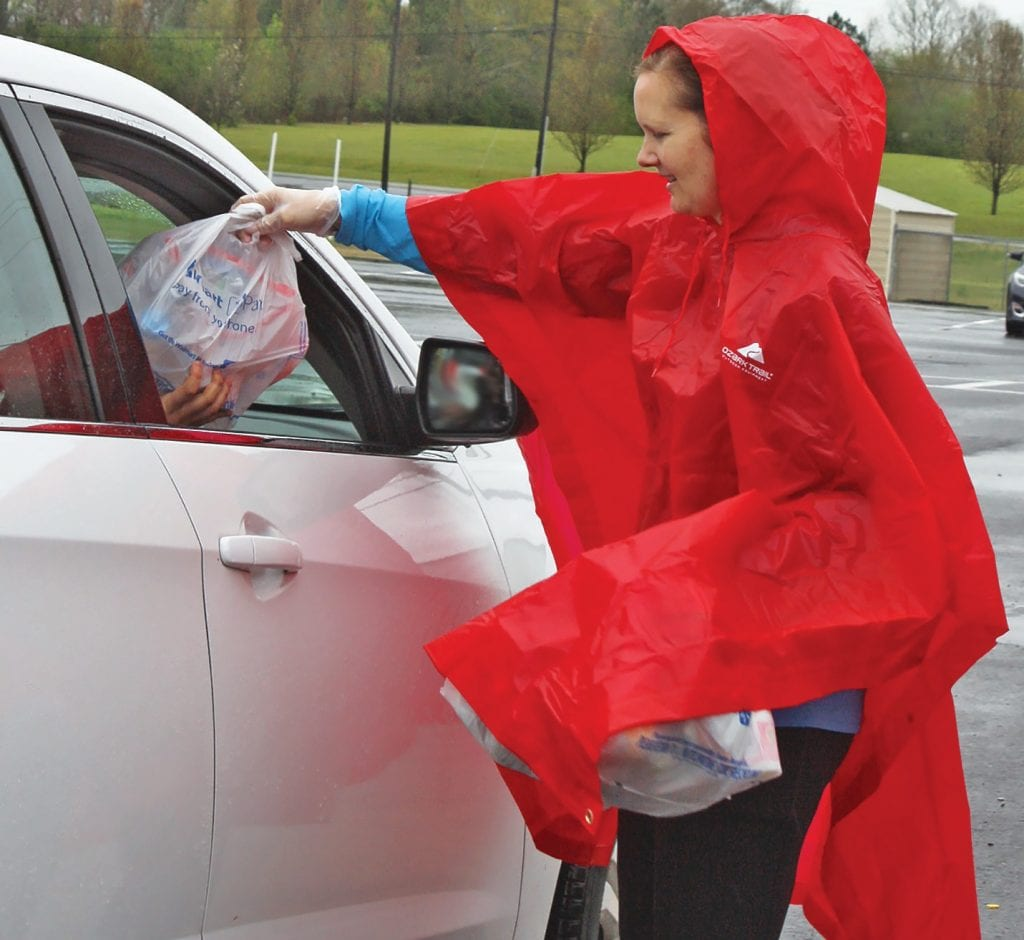 Susan Moore Elementary counselor Patti Gilliland hands off student meals Monday.